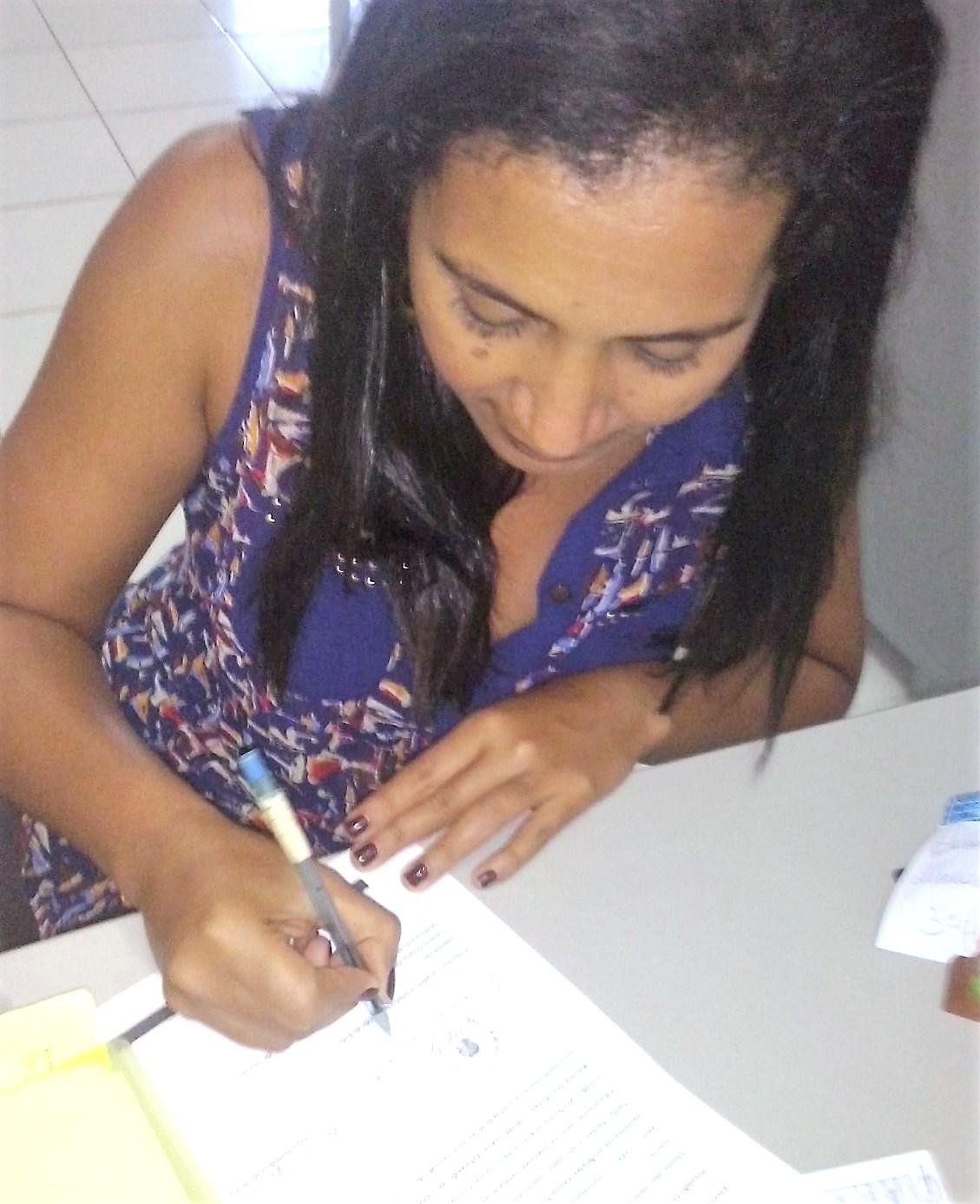 Cristiane Santana, vice-diretora, assinando a Declaração de encaminhamento Turma Sambaituba